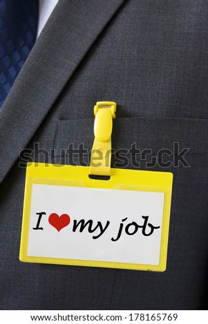 I love my job sign on name card hanging on a dark business suit  - stock photo