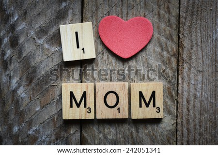 I Love my mom Concept. Red heart and Wooden Scrabble letters spelling I Love my mom Concept. - stock photo