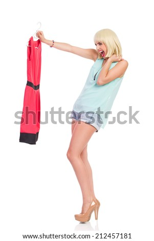 I love my new red dress. Excited blond young woman holding red dress and shouting. Full length studio shot isolated on white. - stock photo