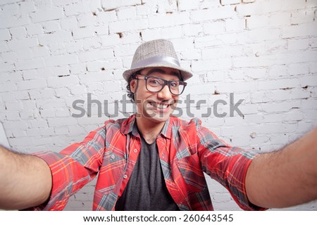 I love selfie! Handsome young Arabic hipster man in shirt holding camera and making selfie and smiling while standing against brick wall - stock photo