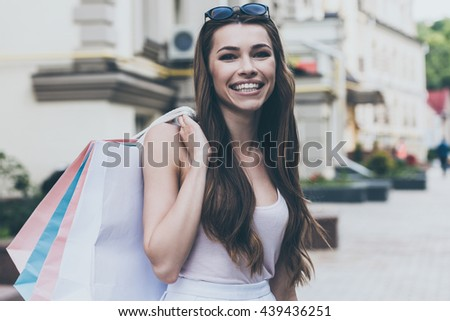 I love shopping! Beautiful young woman carrying shopping bags and looking at camera with smile while standing outdoors - stock photo