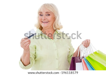 I love shopping! Happy senior woman showing her credit card and holding shopping bags while standing isolated on white background - stock photo