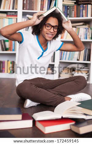 I love studying. Cheerful African teenager holding book on head and smiling while sitting on the floor at the library - stock photo