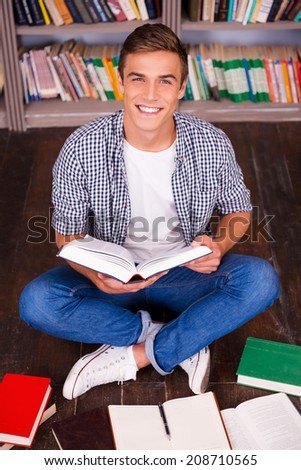I love studying! Top view of happy young man reading book and looking at camera while sitting against bookshelf - stock photo