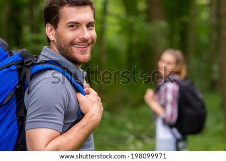 I love traveling. Handsome young man with backpack looking over shoulder and smiling while walking through a forest with woman in the background   - stock photo