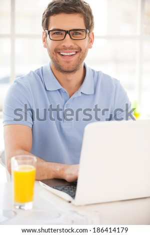 I love working at home! Handsome young man working on laptop and smiling while sitting at the table with glass of orange juice on it - stock photo