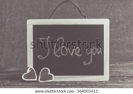 I love you handwritten on a black chalkboard with cookies. - stock photo