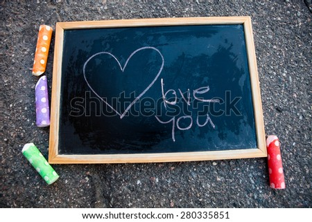I love you message and a heart on chalkboard and colorful street chalk - stock photo