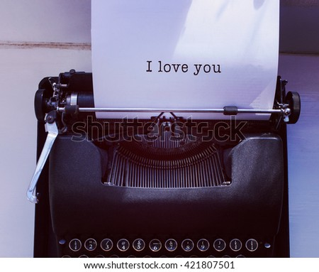 I love you message on a white background against womans hand typing on typewriter - stock photo