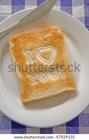 I love you message on toasted white bread on a plate with a knife - stock photo