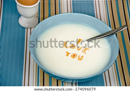 I love you message with cereal floating in white milk in bowl with brown hard boiled egg - stock photo