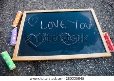 I love you message with hearts on chalkboard with colorful street chalk - stock photo