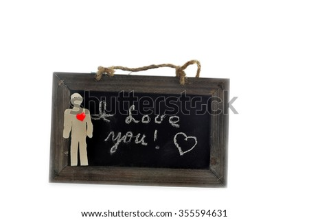 I love you note written on the chalkboard, with a red heart clay man in the foreground - stock photo