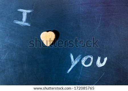 I love you on a scratched school board with candy heart - stock photo