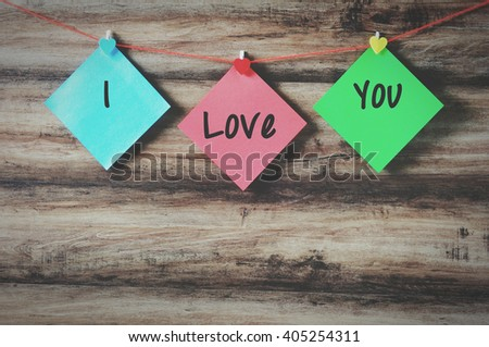 I love you on colorful paper with clothespin hanging on a string with wooden background, retro style. - stock photo