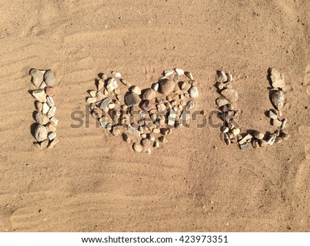 I love you phrase made from stones on sandy background