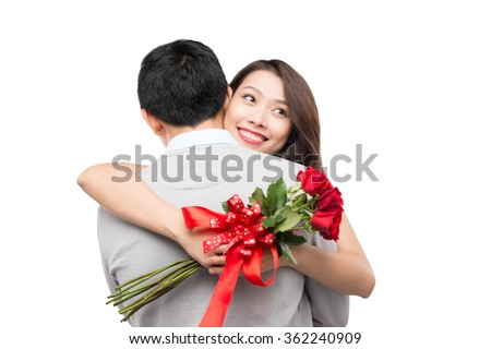 I love you so much! Beautiful young loving couple hugging while woman holding bouquet of pink roses and smiling and both standing isolated on white background.  - stock photo