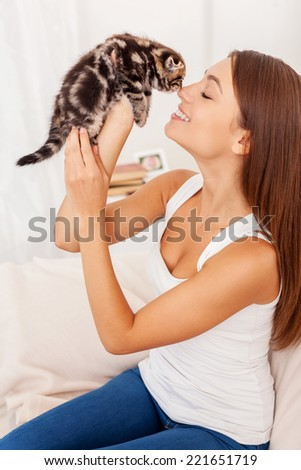 I love you so much! Beautiful young woman holding little kitten in hands and bonding to him  - stock photo