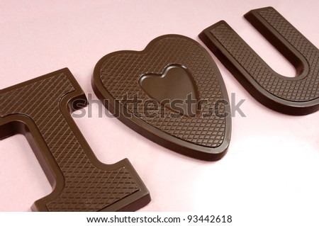 I love you spelled with letters and a heart made of chocolate Valentines Day concept Isolated on pink background - stock photo