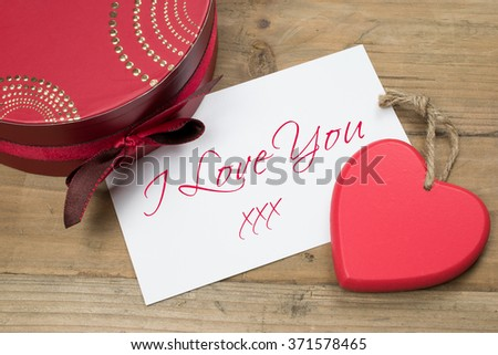 I Love You text card with written message, red wooden heart and luxury gift box.