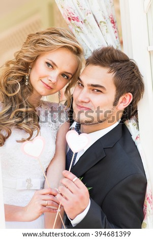 I love you. Wedding couple is holding a card in the shape of heart. They are standing and smiling.  - stock photo