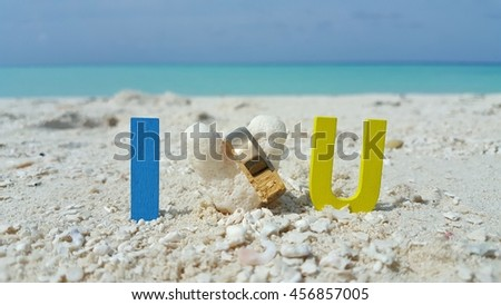i love you word and the gold ring with the beautiful sandy beach and blue sky background - stock photo