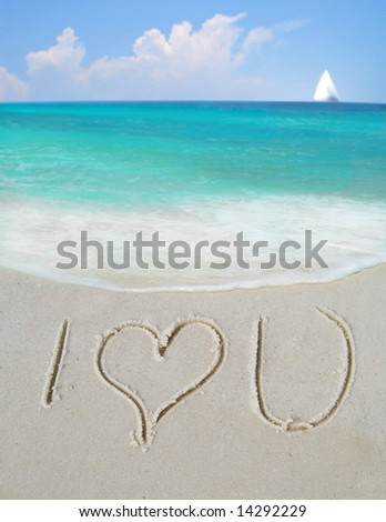 I Love You written in sand by gorgeous ocean with sailboat in distance