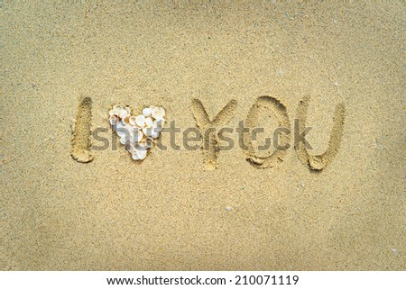I love you written on wet sand on the beach with heart made from sea shells - stock photo