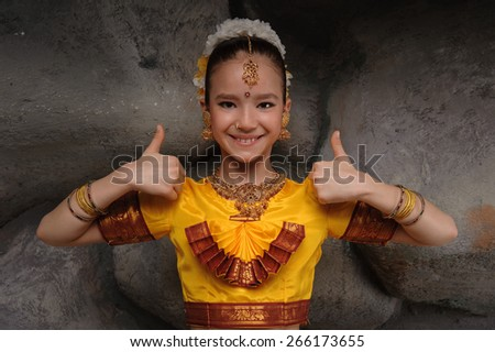 I'm ready to go to dance. beautiful girl dressed in festive costume. shows thumbs up his big fingers - stock photo