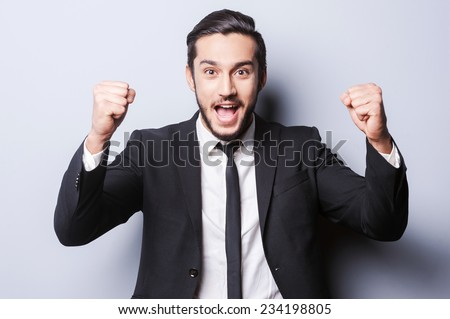 I made it to the top! Happy young man in formalwear gesturing and smiling while standing against grey background - stock photo