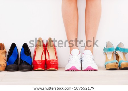 I made my choice! Cropped image of woman in sports shoes standing against the wall while high hilled shoes laying in a row near her - stock photo