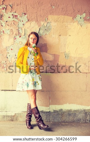 I miss you. A girl wearing flower patterned underdress, yellow corduroy jacket, brown leather high riding boots, holding white rose, smelling, standing by wall peeling off paints, waiting for you. - stock photo