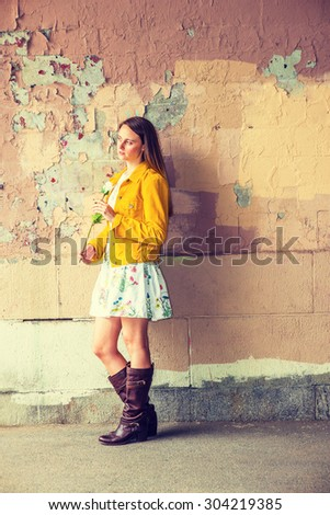 I miss you. A pretty girl wearing flower patterned underdress, yellow corduroy jacket, brown leather high riding boots, holding white rose, standing by wall peeling off paints, waiting for you.  - stock photo