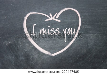 I miss you text and heart sign on blackboard - stock photo