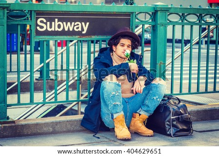 I missing you. Wearing jacket with hood, jeans, boot shoes, Fedora hat, leather bag on ground, a guy with freckle face, sitting on street by Subway sign in New York, smelling white rose, thinking.  - stock photo