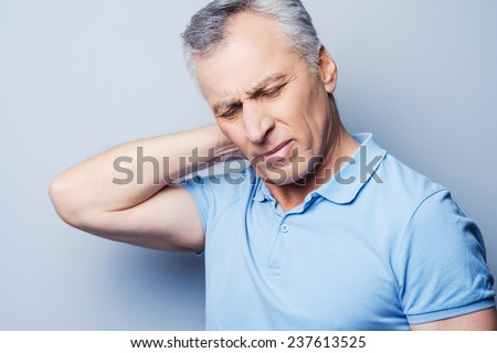 I need a massage. Frustrated senior man in T-shirt holding hand on his neck while standing against grey background - stock photo