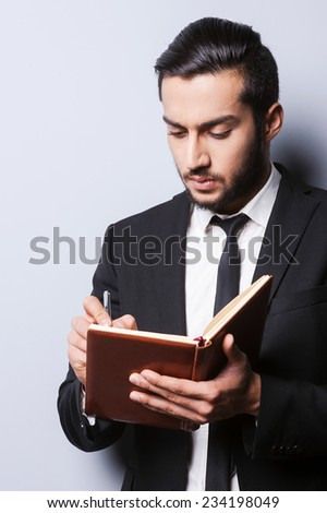 I need some fresh ideas. Concentrated young man in formalwear holding note pad and writing in it with pen while standing against grey background