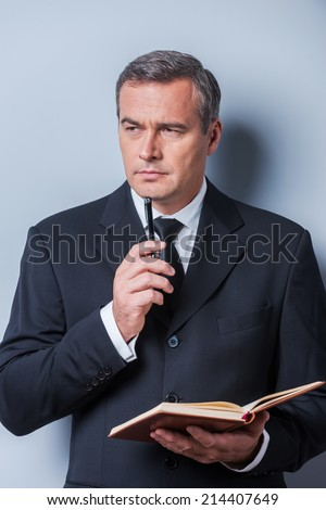 I need some fresh ideas. Thoughtful mature man in formalwear holding note pad and touching his chin with pen while standing against grey background - stock photo