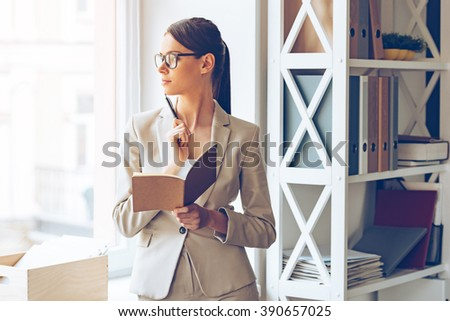 I need to make some changes! Pensive young beautiful businesswoman in glasses holding notebook and looking through window while standing at her working place - stock photo