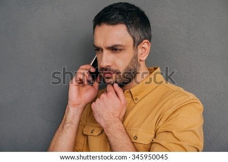 I need to think about it. Thoughtful mature man talking on the mobile phone and holding hand on chin while standing against grey background - stock photo