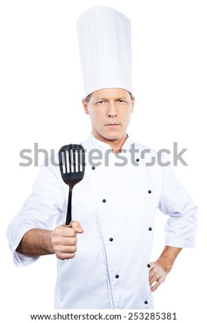 I need you at the kitchen! Confident mature chef in white uniform holding spatula and looking at camera while standing against white background - stock photo