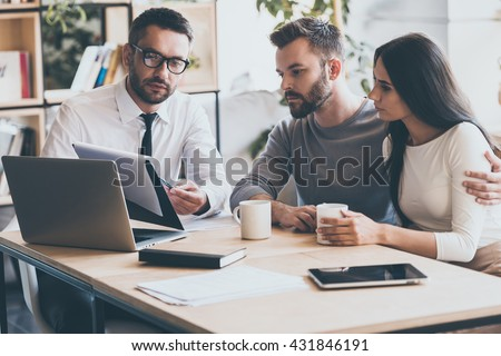 I need your signature here. Confident young man in shirt and tie holding some document and pointing it while sitting together with young couple at the desk in office  - stock photo