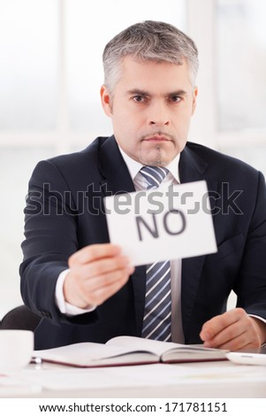I said no! Serious senior man in formalwear holding a paper with no sign on it while sitting at her working place - stock photo