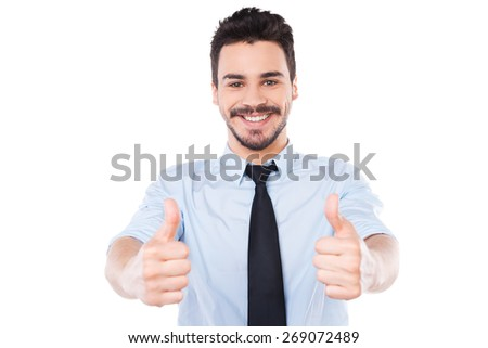 I say yes! Confident young man in shirt and tie looking at camera and showing his thumbs up and smiling while standing against white background - stock photo