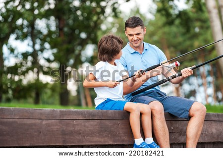 I t is all about right angle. Cheerful father and son fishing while sitting on quayside - stock photo