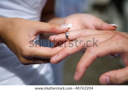 I thee wed - a bride in a white gown puts the ring on the finger of a groom - stock photo