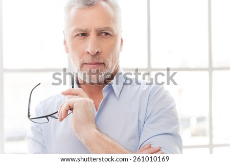 I think I have an idea. Thoughtful grey hair senior man in shirt holding his eyeglasses and looking away while standing in front of the window - stock photo
