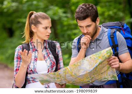 I think we have lost. Thoughtful young man with backpack examining map while angry woman standing near him and gesturing - stock photo