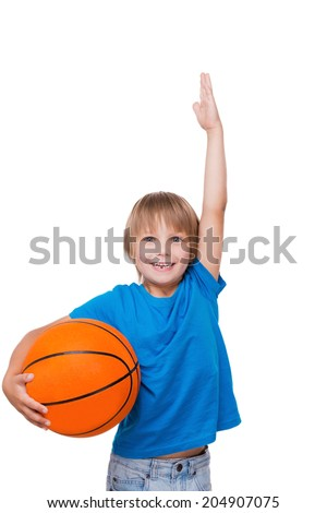 I want to be as tall! Cheerful little boy holding basketball ball and gesturing while standing isolated on white - stock photo