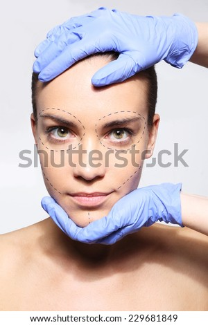 I want to be beautiful! Head of a Woman in the hands of a plastic surgeon.Caucasian woman during surgery using a scalpel - stock photo
